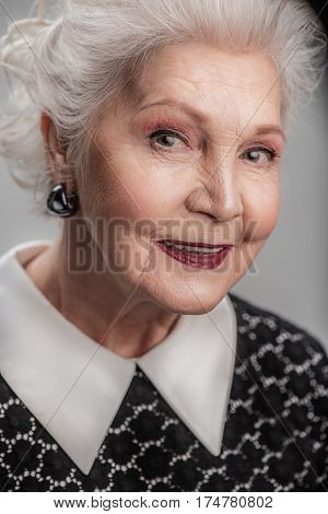 Always have positive on her face. Waist up portrait of beautiful elderly lady daydreaming while staring with gentle smile isolated gray background