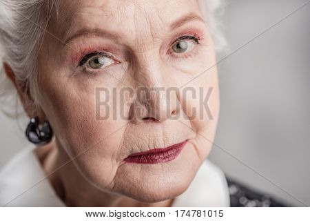 Content in her golden years. portrait of thoughtful senior woman with natural white hair and minimal makeup looking at camera. isolated gray background