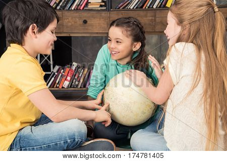 side view of cheerful classmates talking with globe in middle