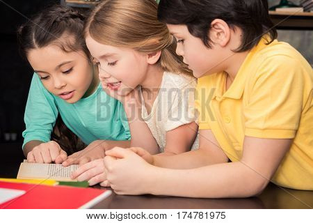 Three schoolchildren leaning at table and reading book together