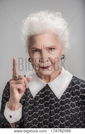 Listen to me carefully. Portrait of confident middle aged woman pointing up one finger while posing isolated background