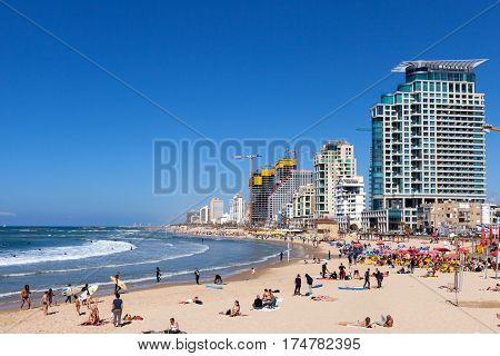 Tel Aviv, Israel - March 4, 2017:  Tel Aviv's coastline with sea front hotels and buildings and people at the beach.