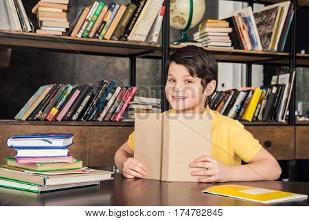 Cute schoolboy holding book in library and smiling at camera