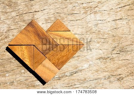 Tangram puzzle in heart shape on wooden background