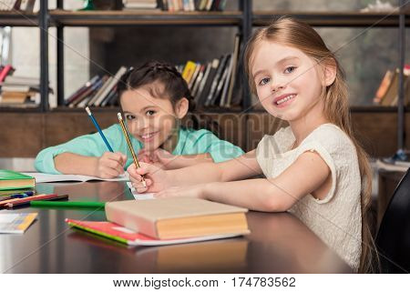 Cute little schoolgirls sitting at table with books and smiling at camera