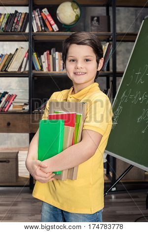 Schoolboy holding books while standing near chalkboard and smiling at camera