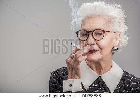 Feeling nostalgic. Portrait of smiling older woman with glasses holding cigarette in her hand while posing. Isolated on gray background and copy space in left side