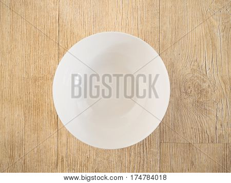 White ceramic bowl or plate on a wood deck.