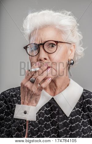 Still young. Portrait of good looking senior woman wearing glasses with expressive face and smoking cigarette. isolated on gray background