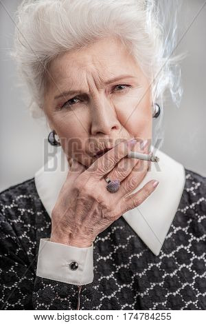 Stressful time. Portrait of Modern old lady looking at camera and smoking cigarette. isolated on gray background
