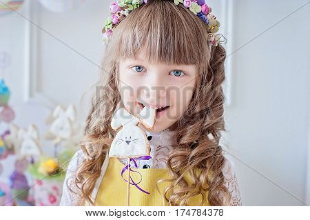 Little girl eats a gingerbread cookie in the shape of the Easter bunny. Easter celebration.