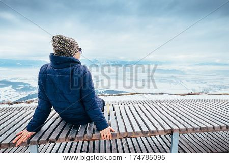Woman relax on top hill point with beautiful panoramic view of winter city