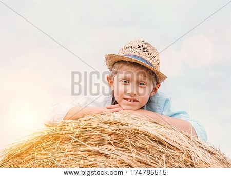 Boy in straw hat lying on the haystack