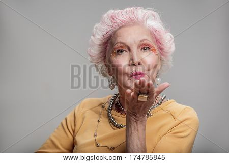 Make every moment count. Portrait of Beautiful middle aged woman blowing while sending air kiss. isolated on gray background