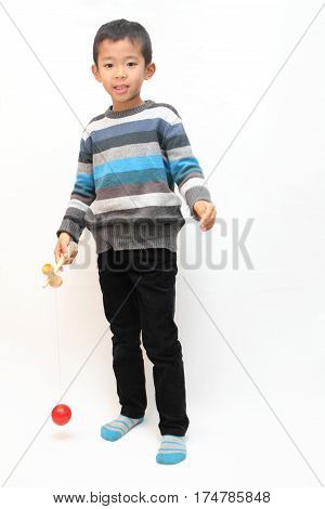 Japanese Boy Playing Cup And Ball (first Grade At Elementary School)