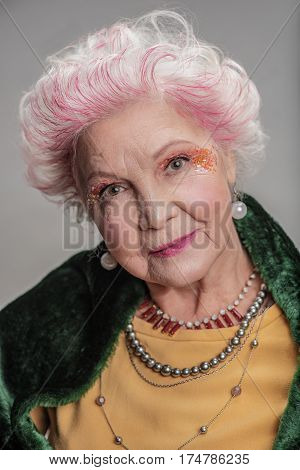 Beauty is being best you at any age. Portrait of Fashionable senior woman with bright makeup and expensive fur cape posing for photographer. isolated on gray background