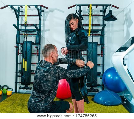 The female athlete doing they exercise in the EMS fitness studio with personal male instructor