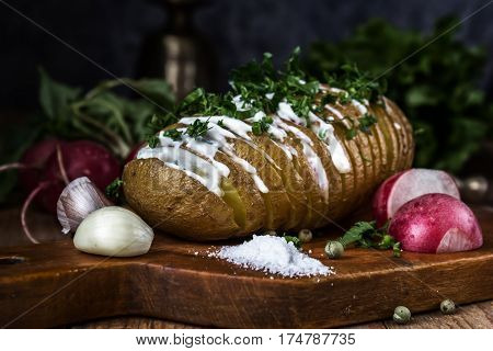 Baked potatoes with sauce, garlic and radish. Still life. Rustic, moonlight, magical light, low key