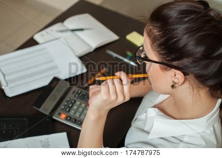 Young female bookkeeper considers on calculator
