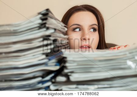 Female bookkeeper with large stacks of documents