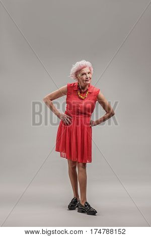 Aging positively well. Stylish senior woman in fashionable dress with hands on hips standing and smiling. isolated on gray background
