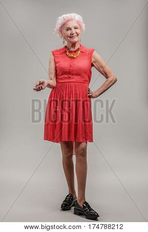 Pretty in red dress. Full length portrait of Vivacious beautiful grey haired elderly woman full of vitality looking up at camera. isolated on gray background