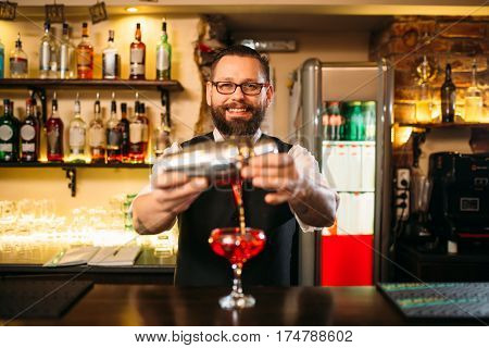 Barman is making alcohol cocktail at counter