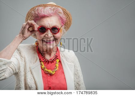 Happy souls never age. Waist up portrait of Smiling fashionable old woman in red sunglasses wearing fashion clothes while posing for photographer. isolated on gray background. Copy space