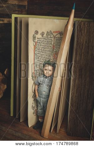 Little boy reading a book study knowledge symbol bibliophile. Funny boy holding a pencil and stand near the huge book. Child opened a magic book. Magic book land