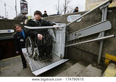 Worker Of The Underground Is  Helping To The Disabled Person