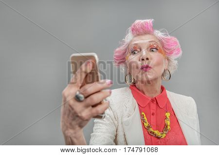 Salute to everyone. Portrait of Senior attractive happy woman with pink hair sending kiss while making selfie and standing against gray background