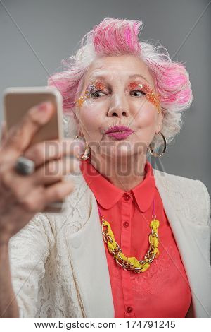 My playful mood today. Cheerful elderly lady making selfie and sending kiss while standing in studio isolated on gray background