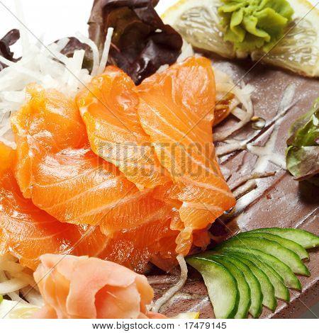 Salmon Sashimi - Sake (fresh raw salmon) on Daikon (White Radish). Garnished with Ginger, Wasabi, Seaweed, Cucumber, Salad Leaf and Lemon