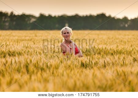 Girl enjoying in a countryside scenic. Girl standing in a wheat field and enjoying the sunset. A relaxing walk on the field. Happy young peasant girl.