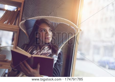 Beautiful young woman sitting in a cafe next to a window thinking and reading a book