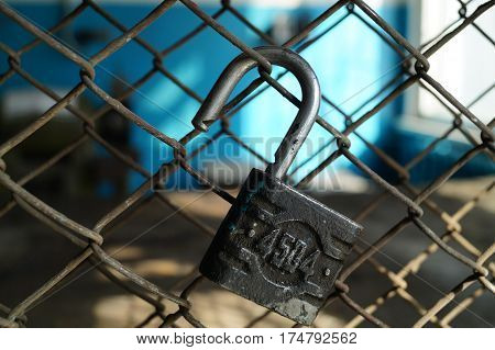 open the padlock on a metal grid