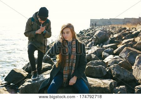 Beautiful And Stylish Couple Walking On A Rocky Beach. Couple Dressed In Jackets, Hats And Boots