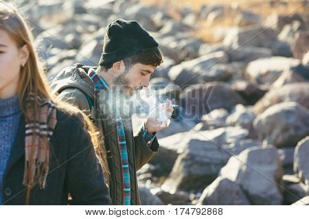 Stylish Portrait Smoking Guy Who Walks With The Girl On The Rocky Shore Of The Sea.