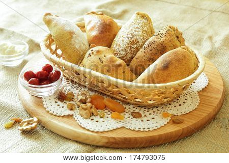 Russian pirozhki, baked patties or pies on basket with nuts and dried apricots