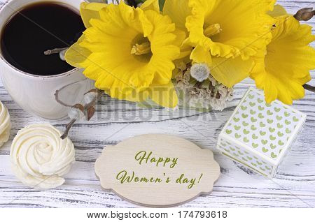 Cup Of Coffee With Marshmallow, Green Gift Box, Yellow Flowers On White Wooden Background And Letter