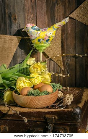 Vertical studio shot of the daylight yellow tulips and eggs in bowl with textile bird over it. Easter composition