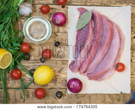 Raw pork meat with herbs and spices on a wooden table. Home cooking with natural products.