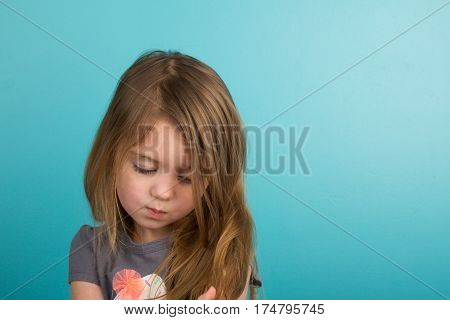 Sad little girl against plain teal background