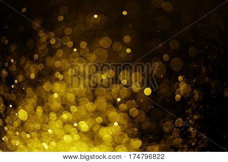 Glitter light gold bokeh blurred black background