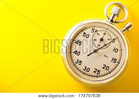 Stopwatch on the yellow background in closeup