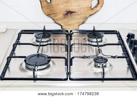stove top of a domestic kitchen with a wooden plate