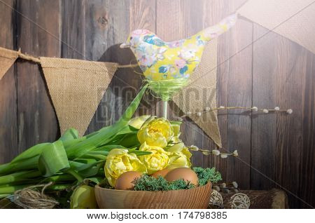 The textile bird over the yellow flowers and wooden bowl with eggs. Horizontal studio shot. Easter still life