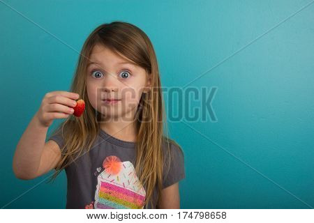 Little girl showing a strawberry with excitement