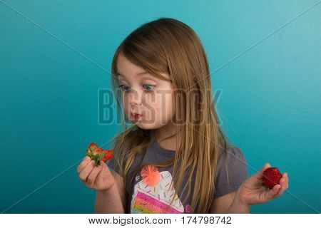 Little girl tasting a strawberry against teal background