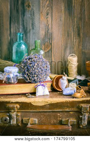 The bunch of dry lavender with different objects on a table in daylight. Vertical studio shot. Vintage still life